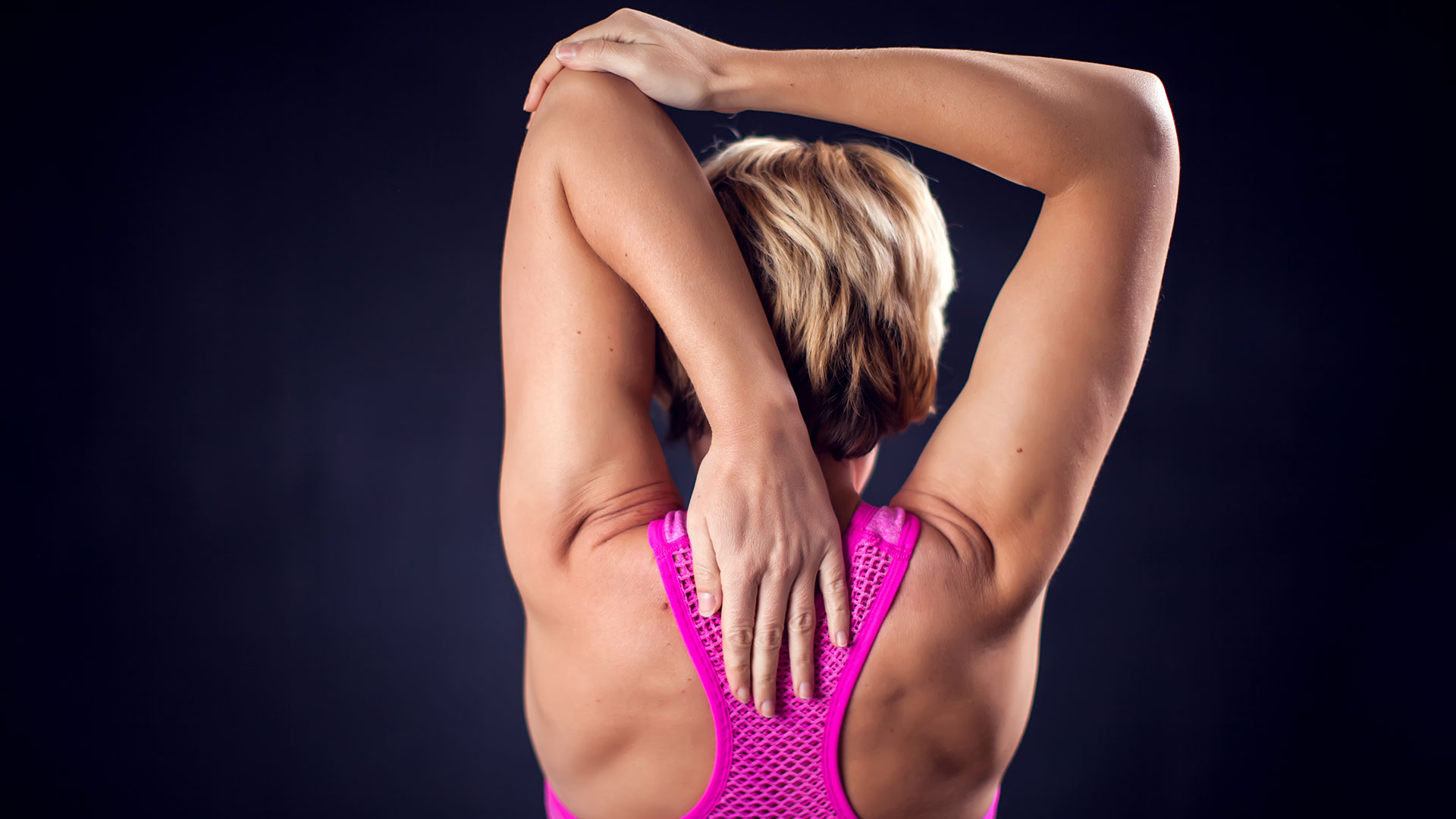 Woman in pink sports top stretches her tricep.