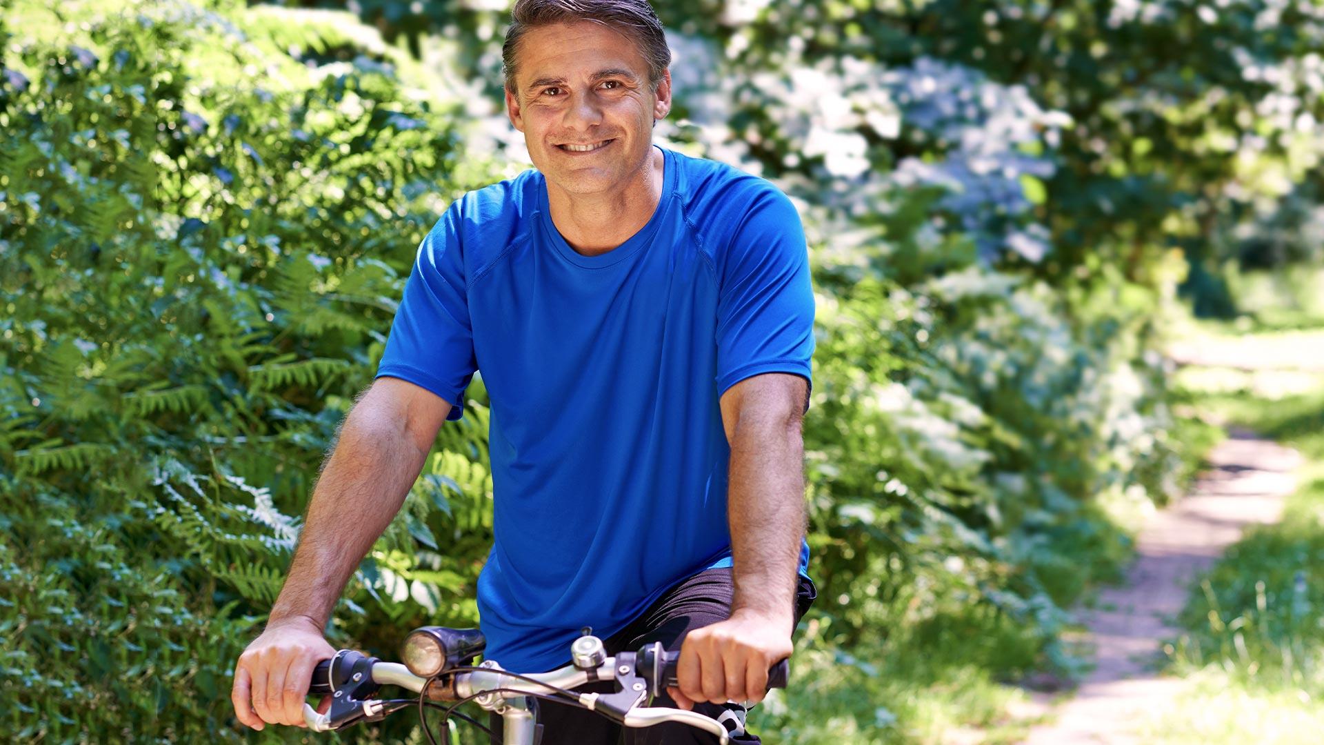 Man riding bike with blue shirt on path