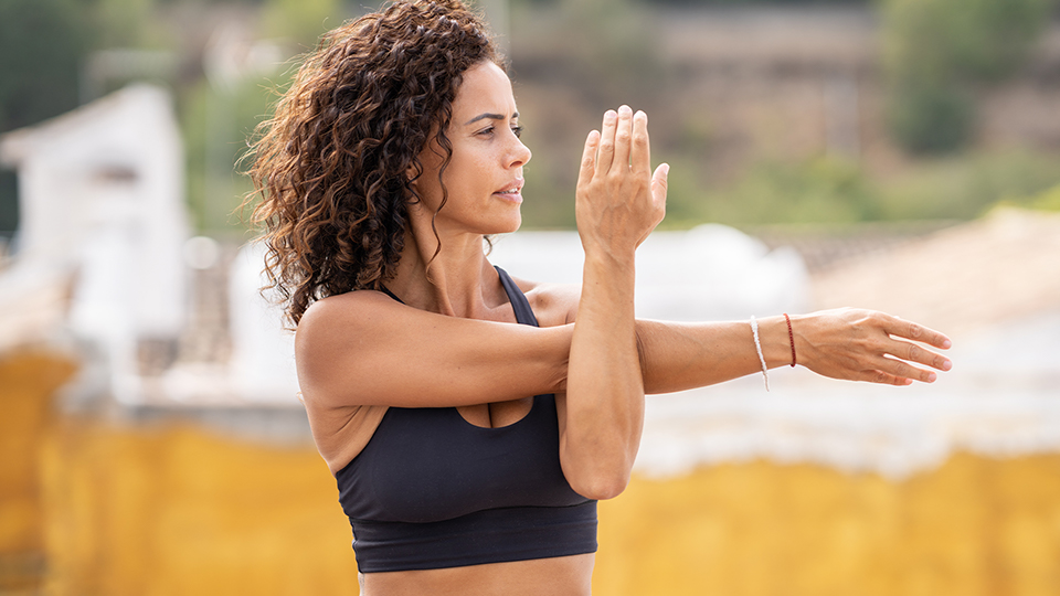 Curly haired woman in her 40s doing Yoga outside