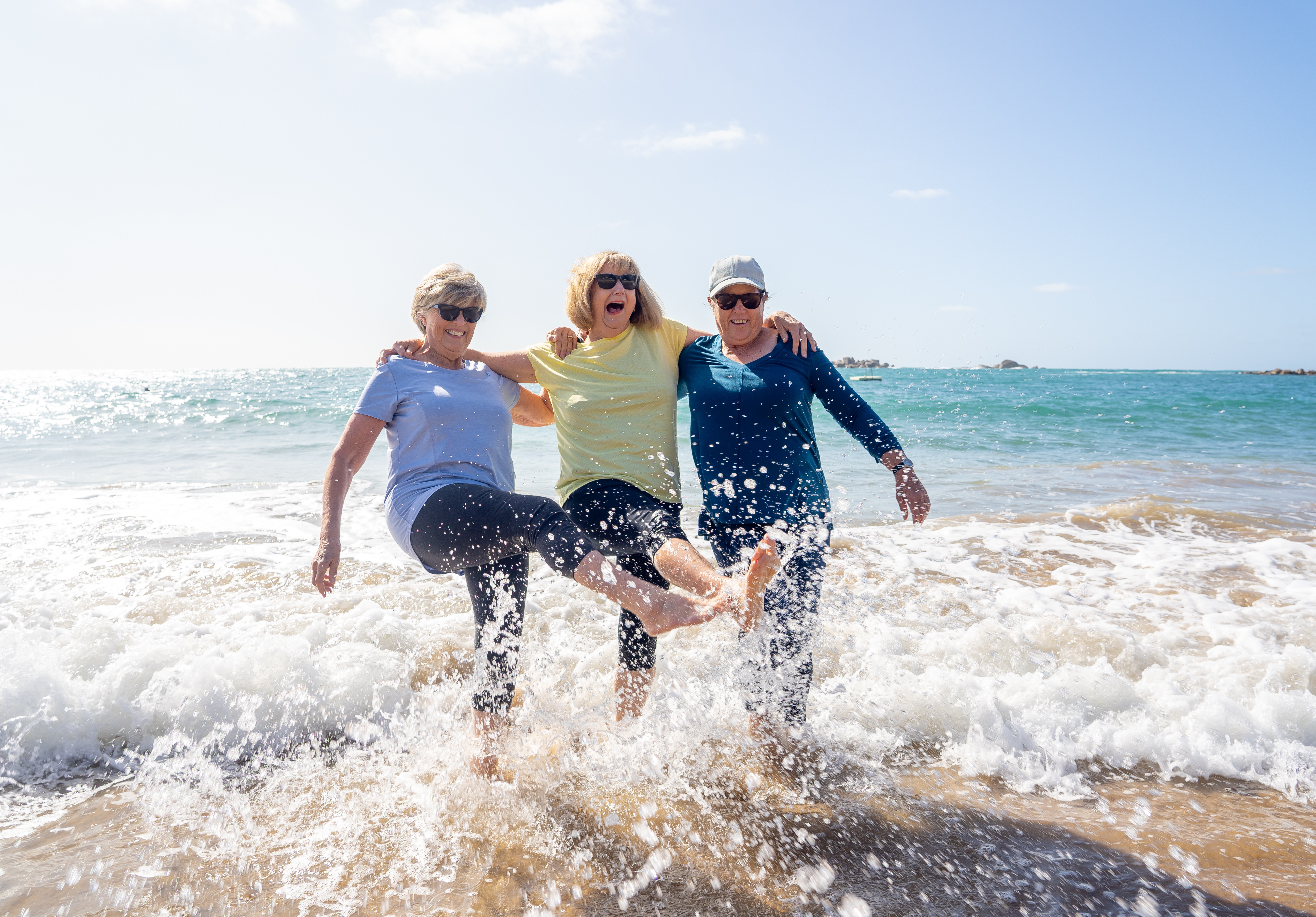 3 midlife women on ocean beach with arms around each other and kicking feet in water