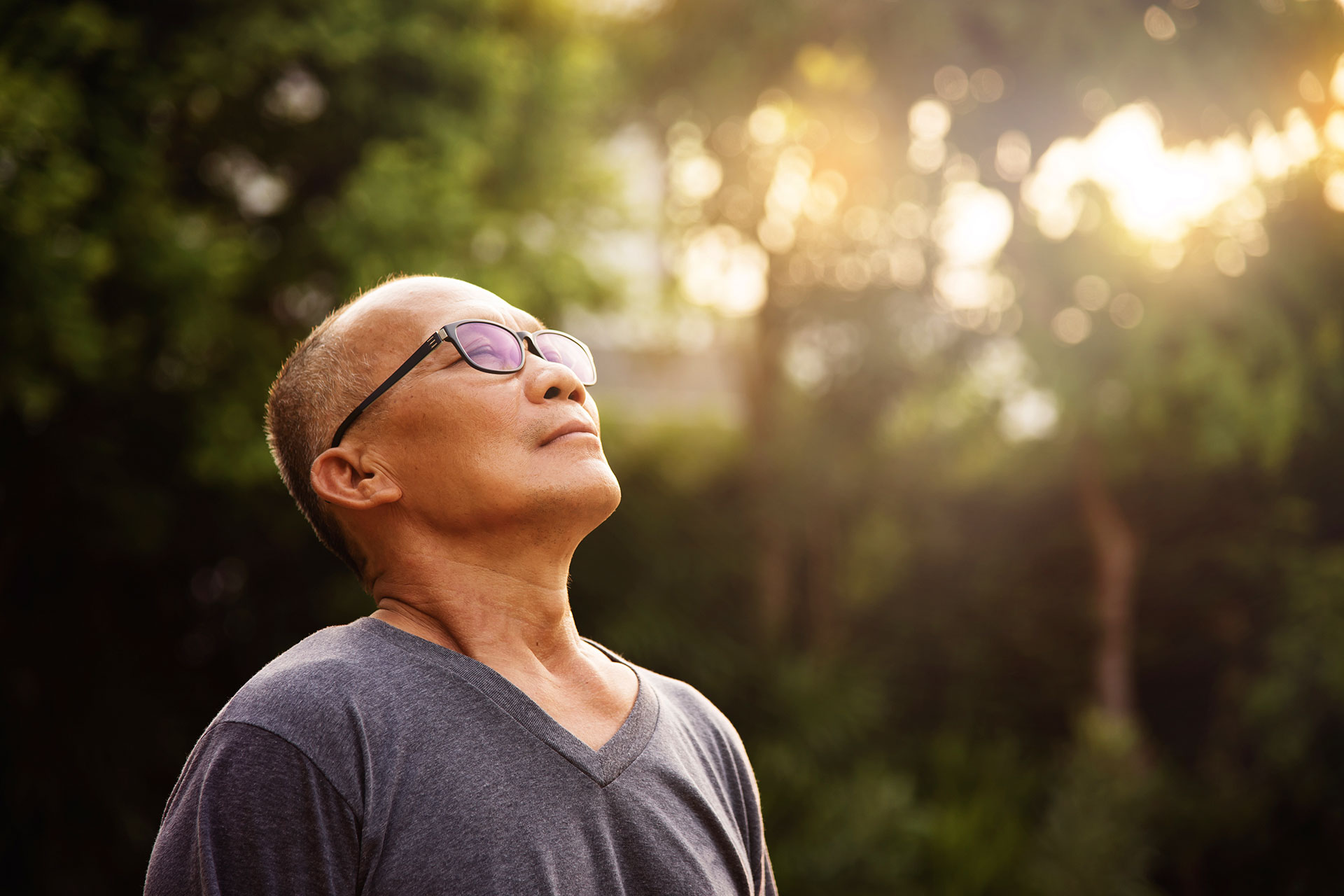 Man taking a deep breath of fresh air with his eyes closed and head tilted back, basking in the golden morning light.