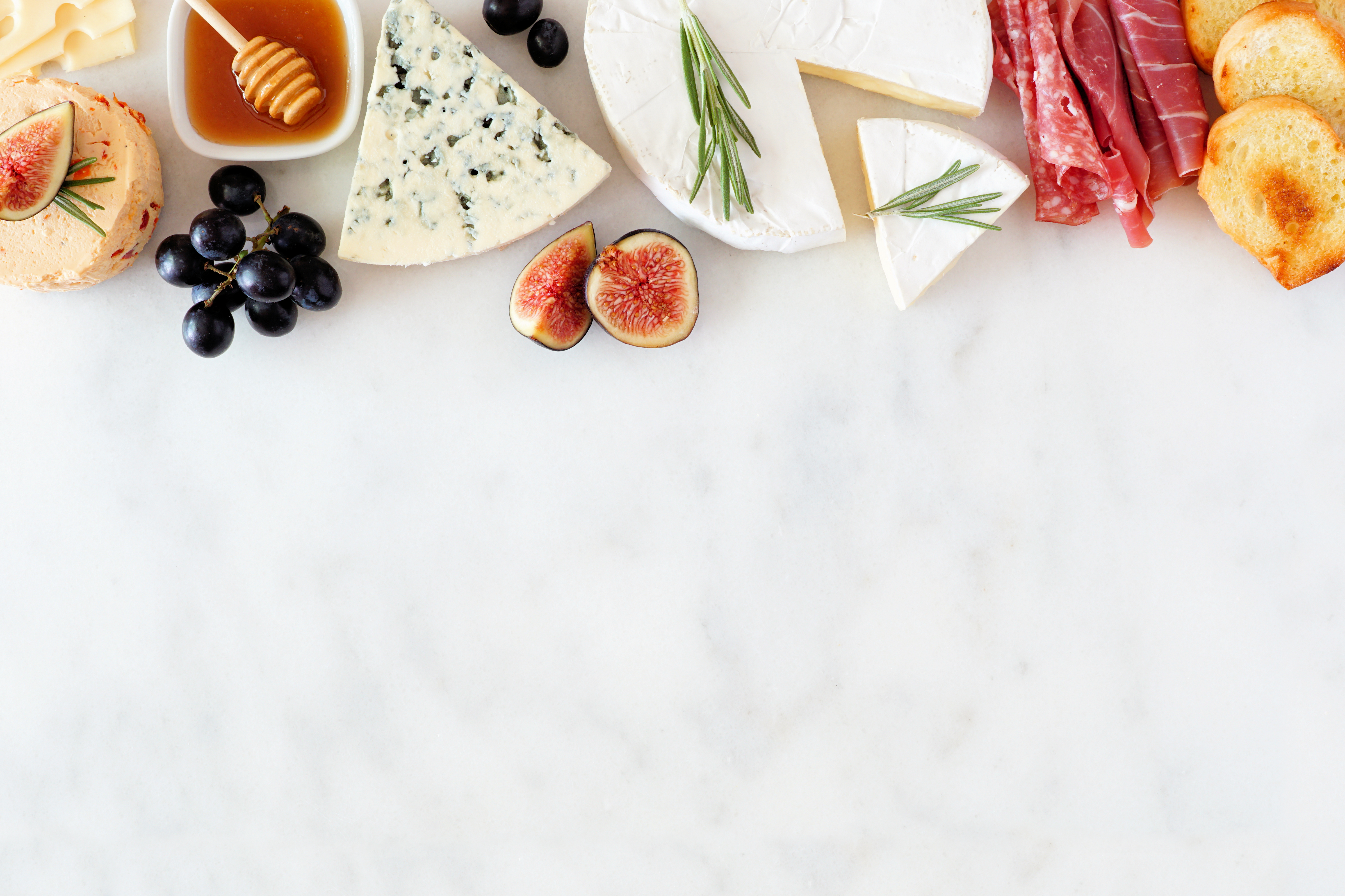 Typical French ingredients (cheeses, meats, a dish of honey, grapes, figs, and bread) arranged decoratively.