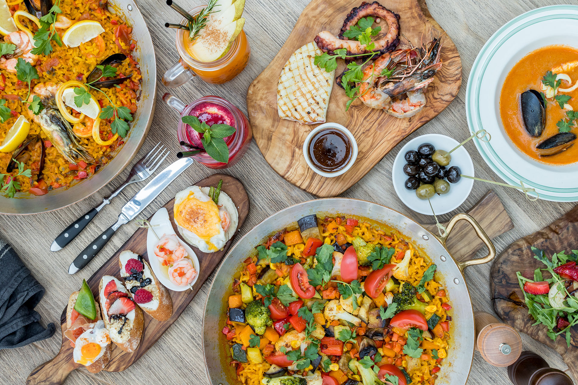 A table arranged with Spanish food featuring vegetable paella, tapas, grilled seafood, and olives.