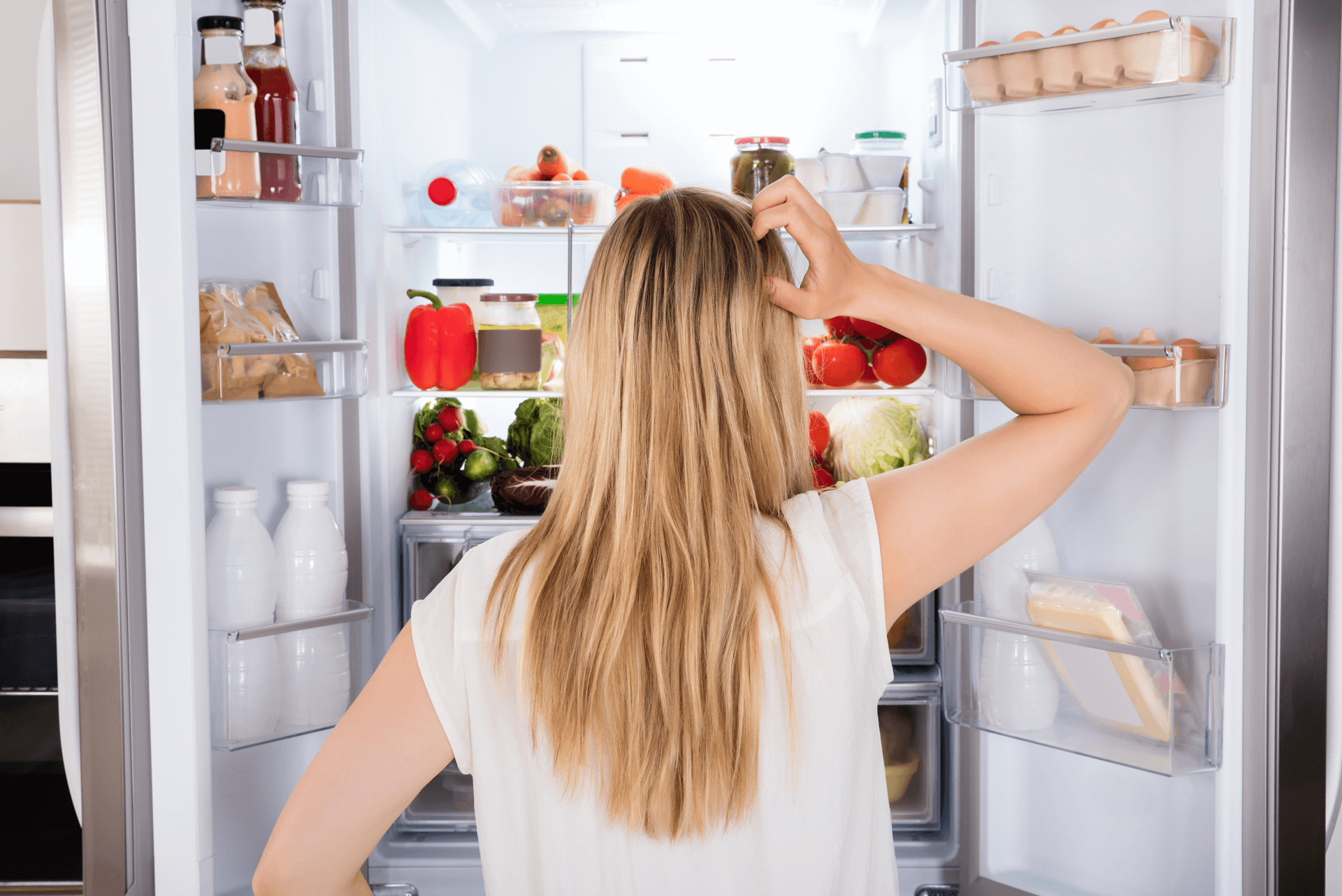 Woman looking into refrigerator deciding on what to eat