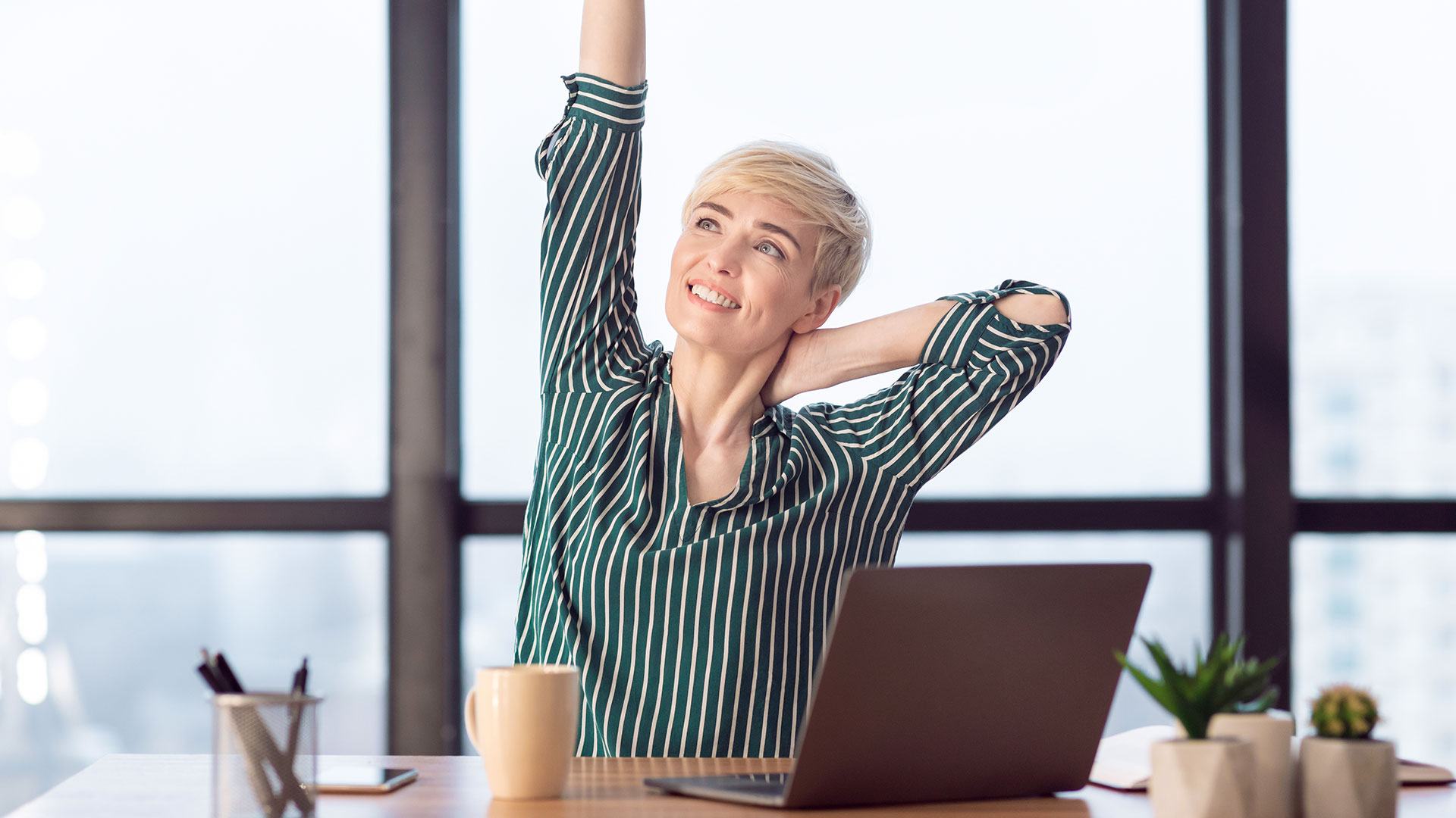 Woman in an office stretches her arms and neck while seated in her desk chair.