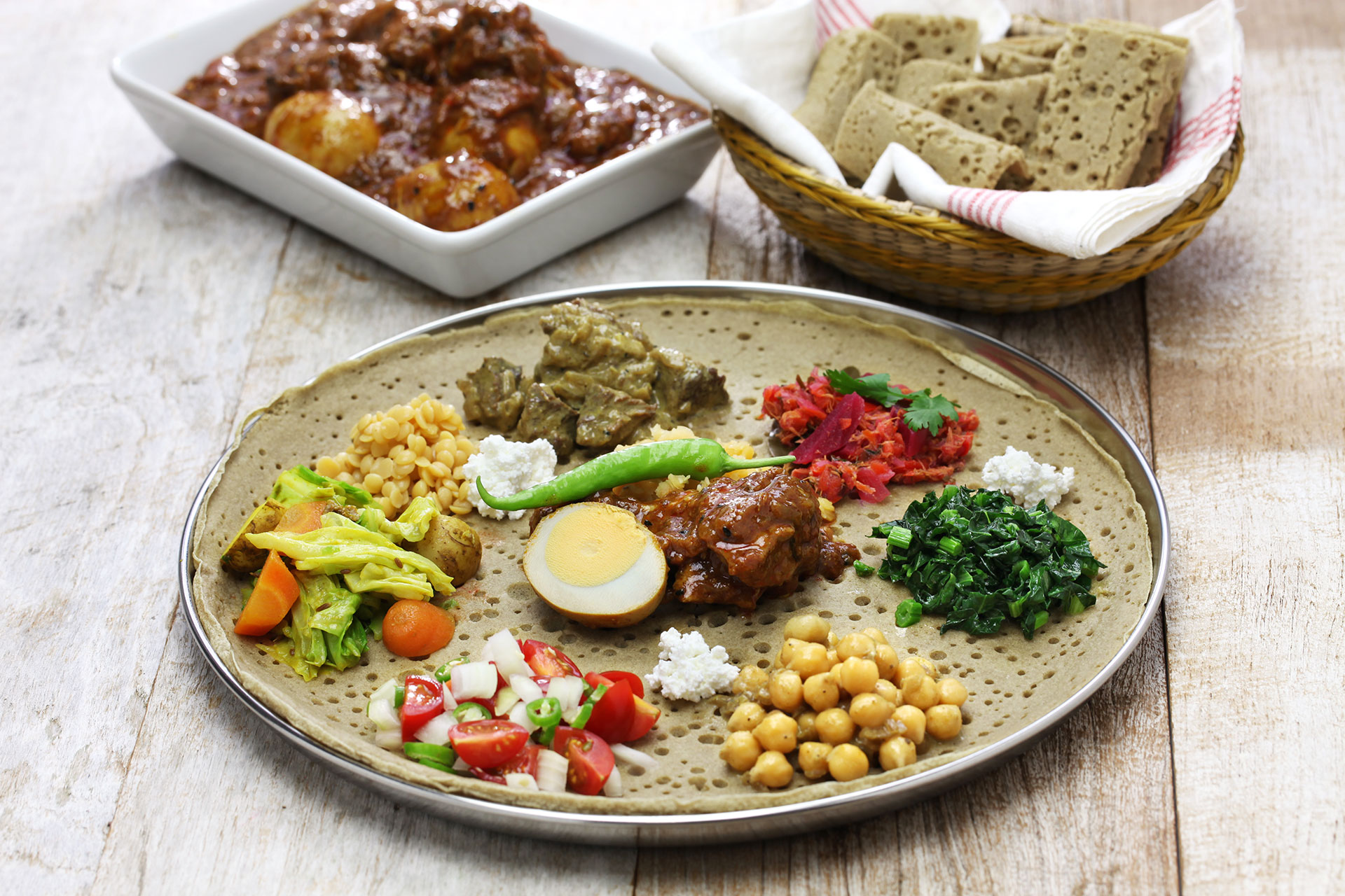 A plate of fresh, colorful Ethiopian food with adjacent dishes of meat stew and a basket of traditional flatbread.