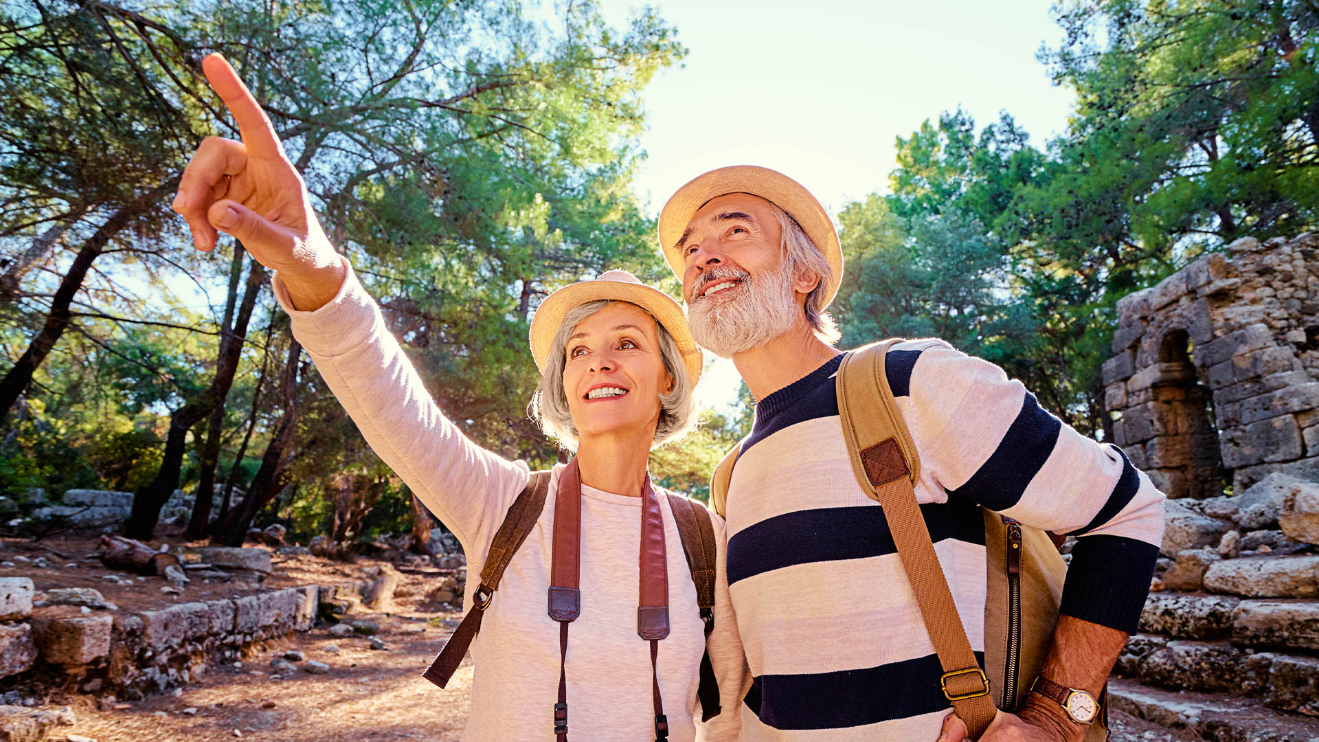 An older couple wearing hats and backpacks, the woman with a camera around her neck, enjoying nature while out on a hike.