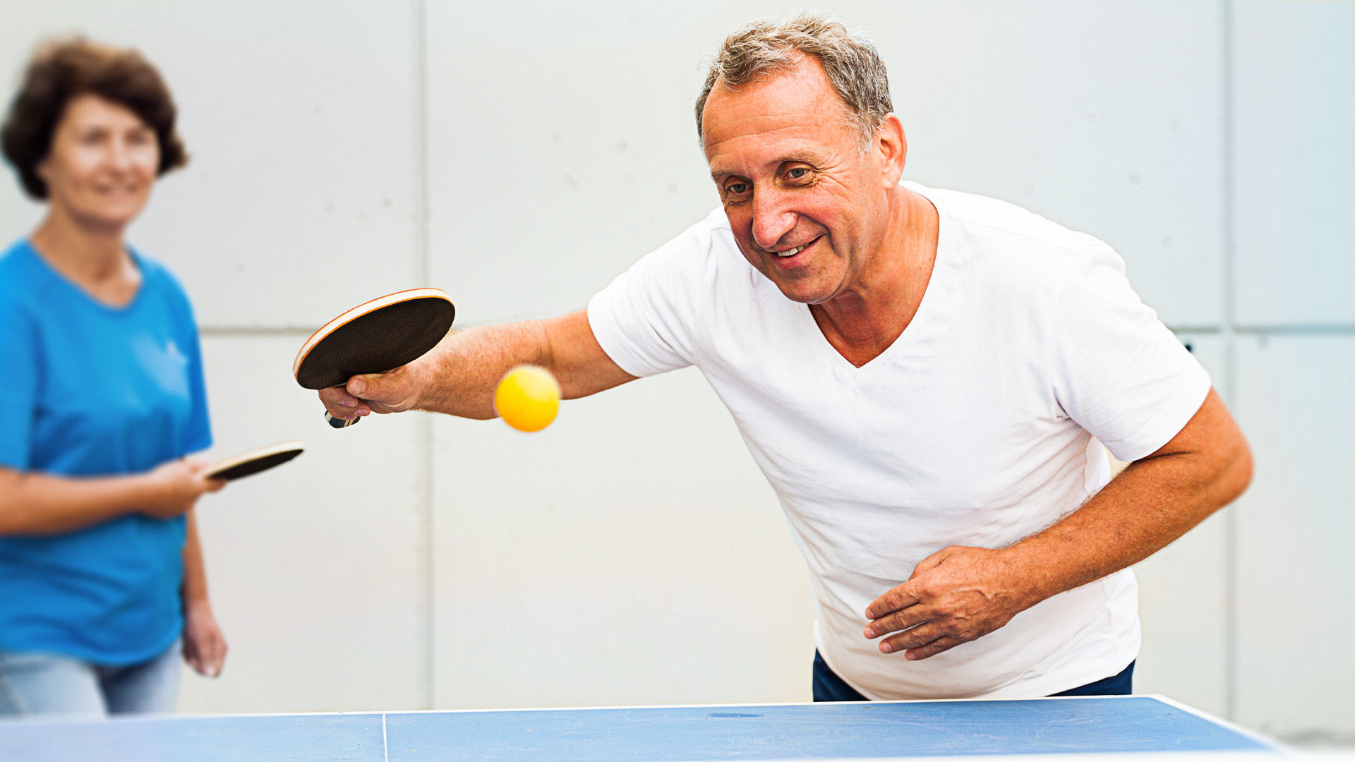 An older man and woman playing ping pong.