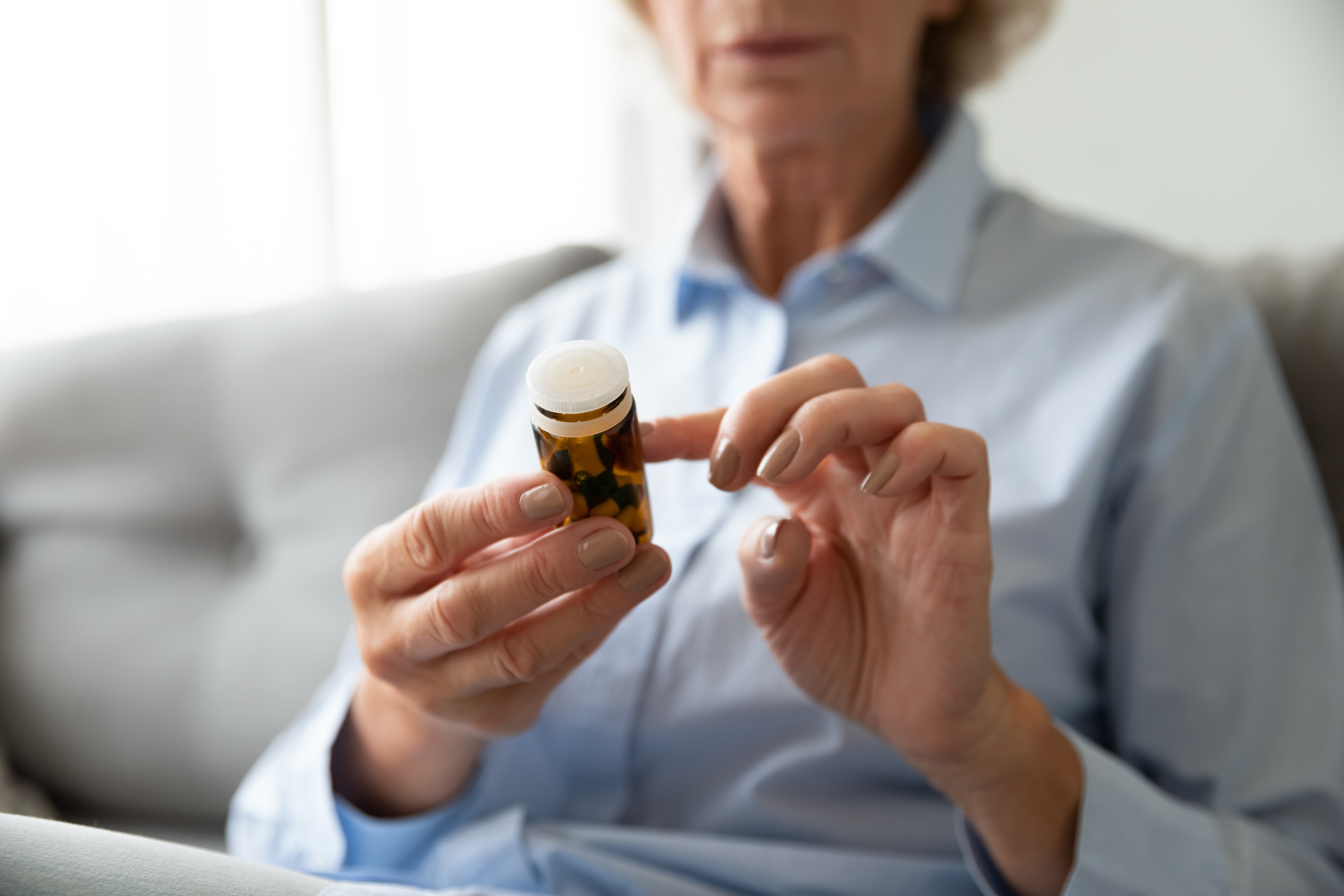 Woman looking at pill bottle