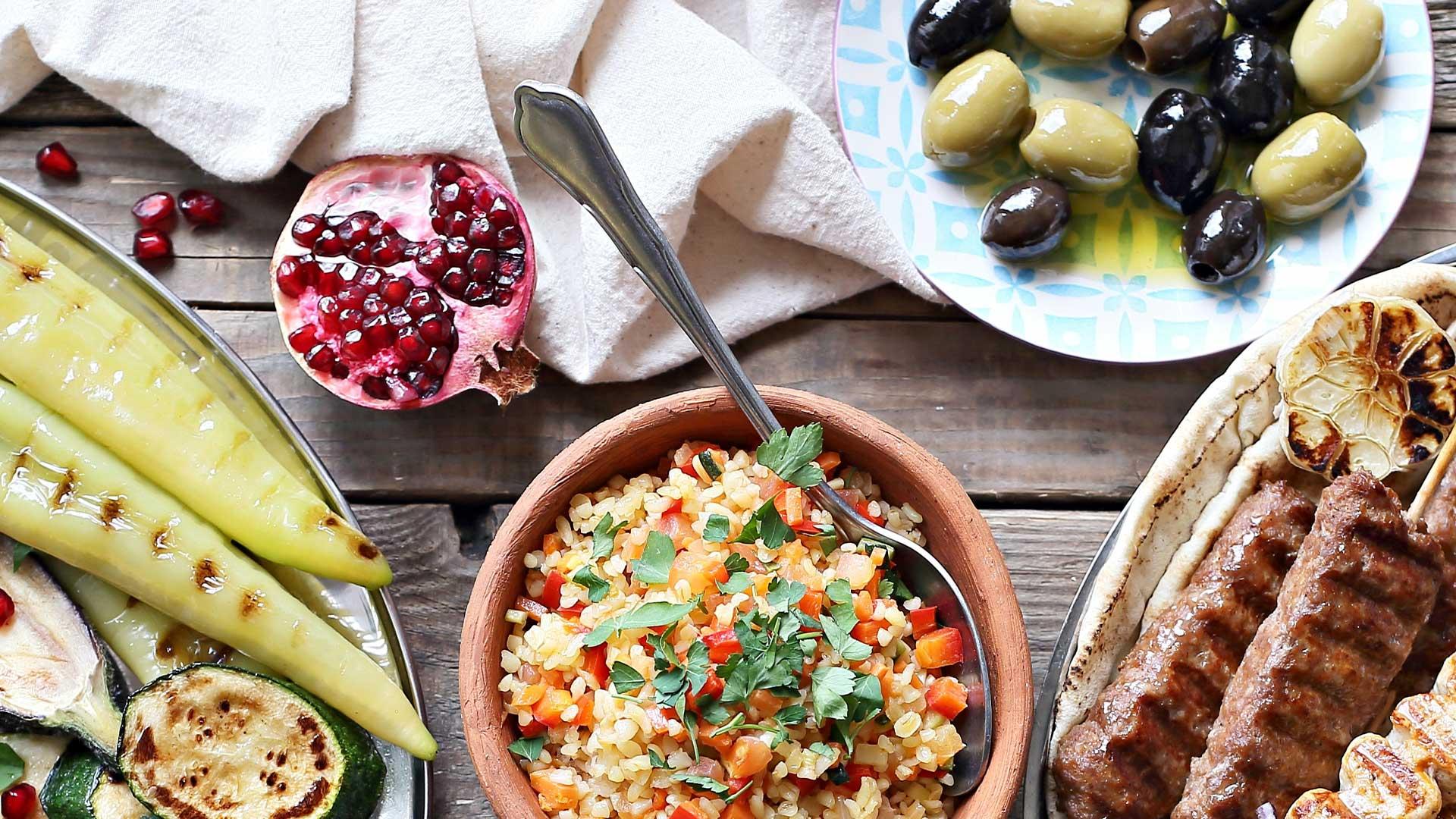 A table of Mediterranean food including grain salad, olives, pomegranate, and grilled vegetables.