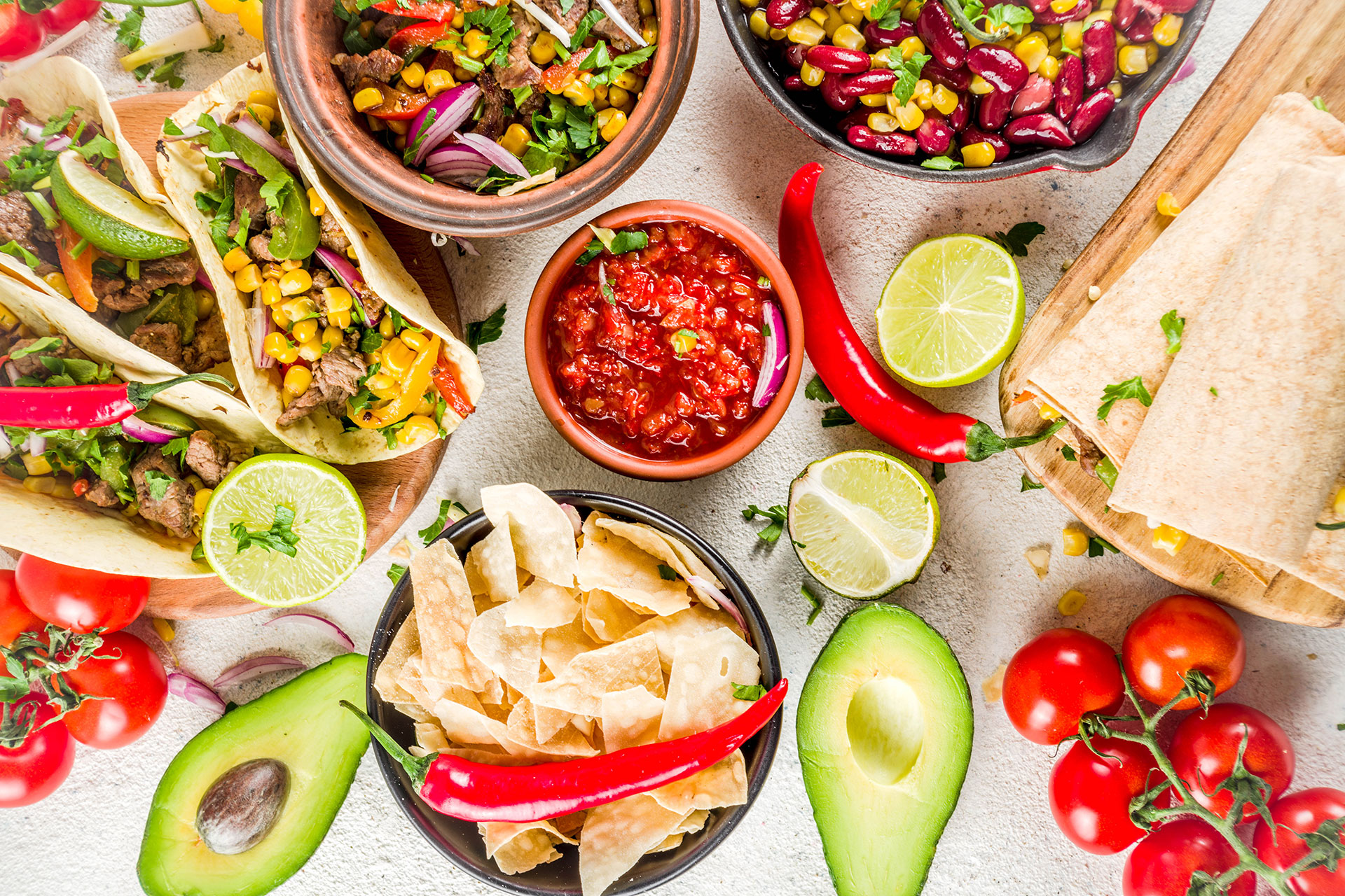 Colorful Mexican food including tacos, tortilla chips, salsa, avocados, limes and other produce laid out on a table.