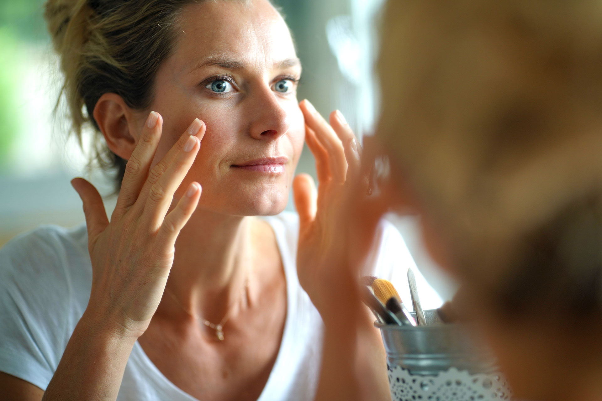 A woman looks in the mirror and carefully applies a skincare product to her cheekbones.