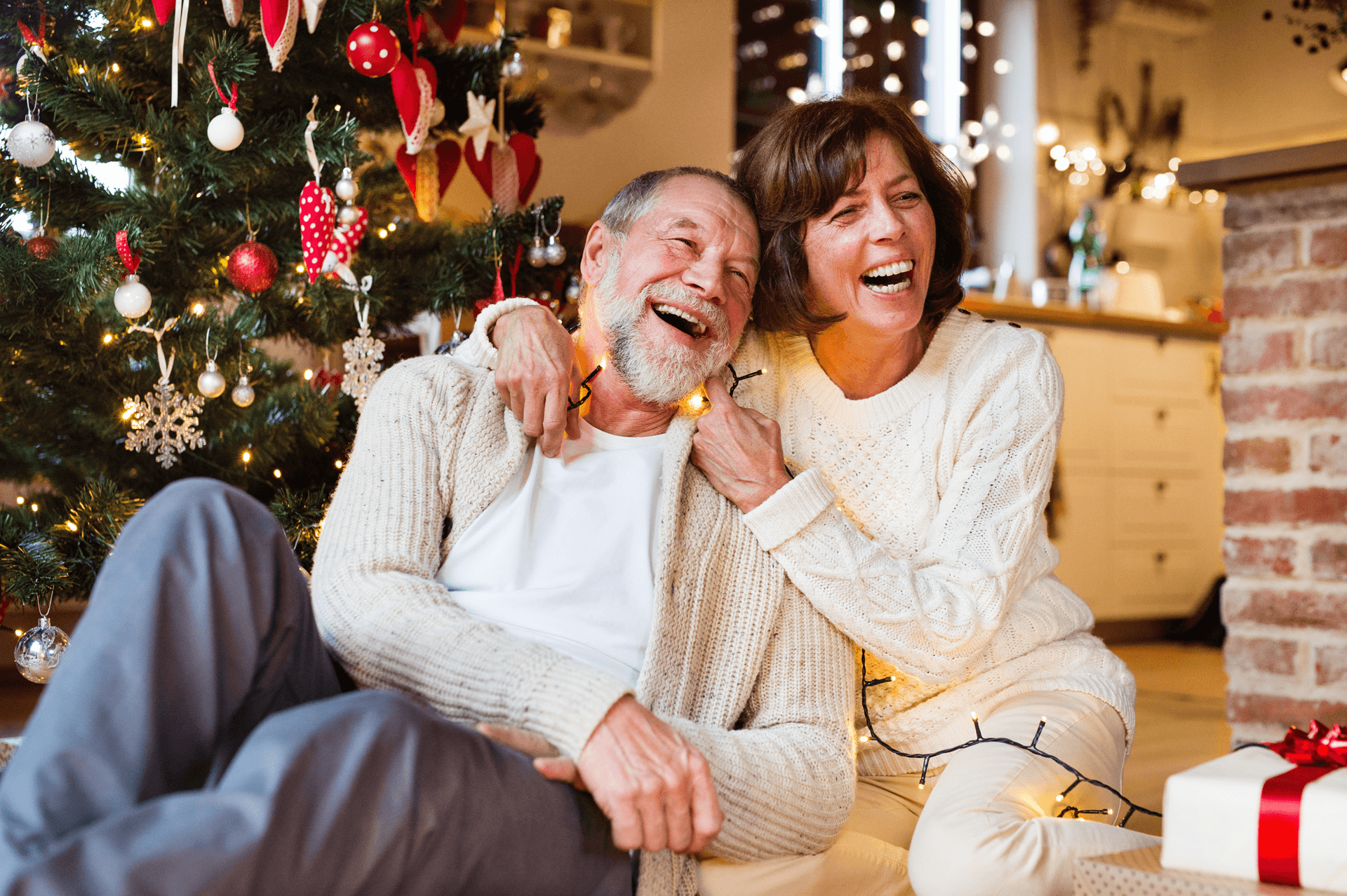Happy middle aged couple by Christmas tree