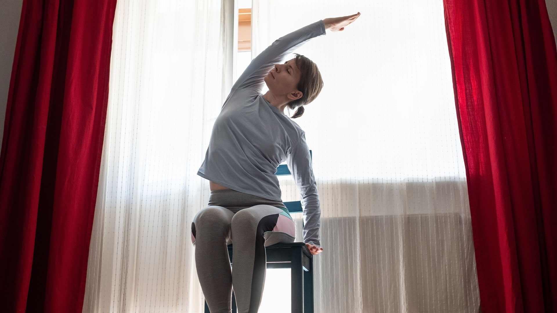 Woman in grey workout clothes stretches her side while seated in a chair.
