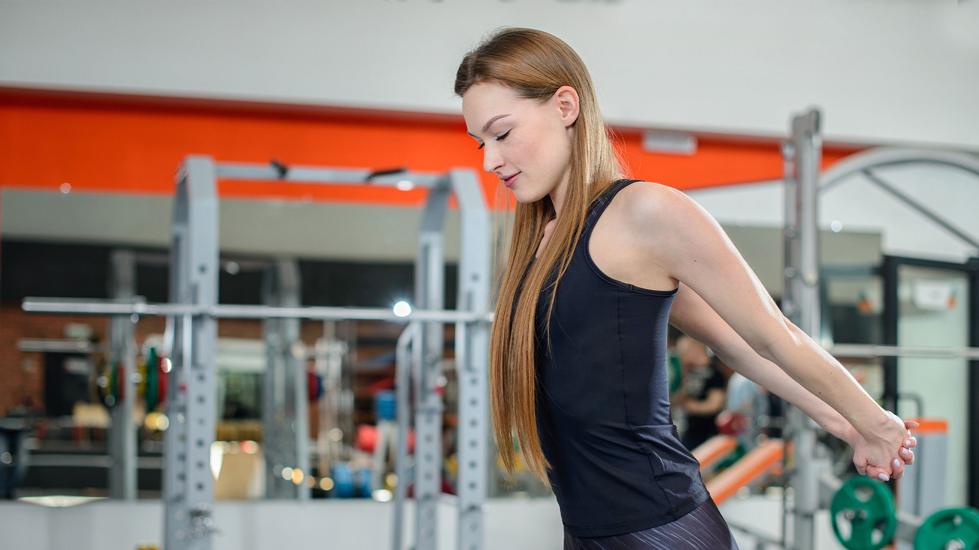 Woman at the gym stretches her chest with her arms extended and hands clasped behind her.