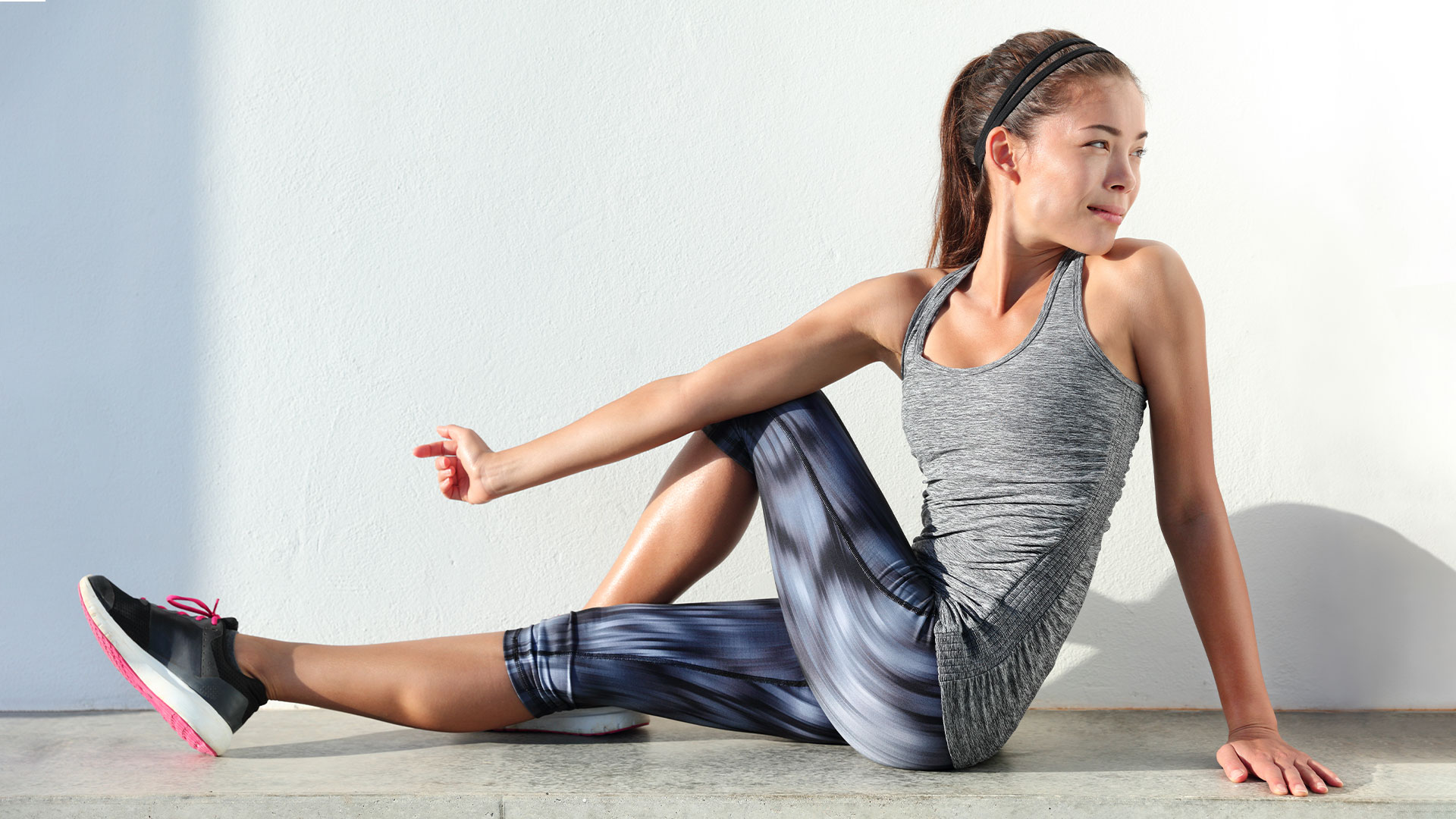 Woman in workout clothes is seated on the ground with legs outstretched and twists her upper body to stretch her torso.