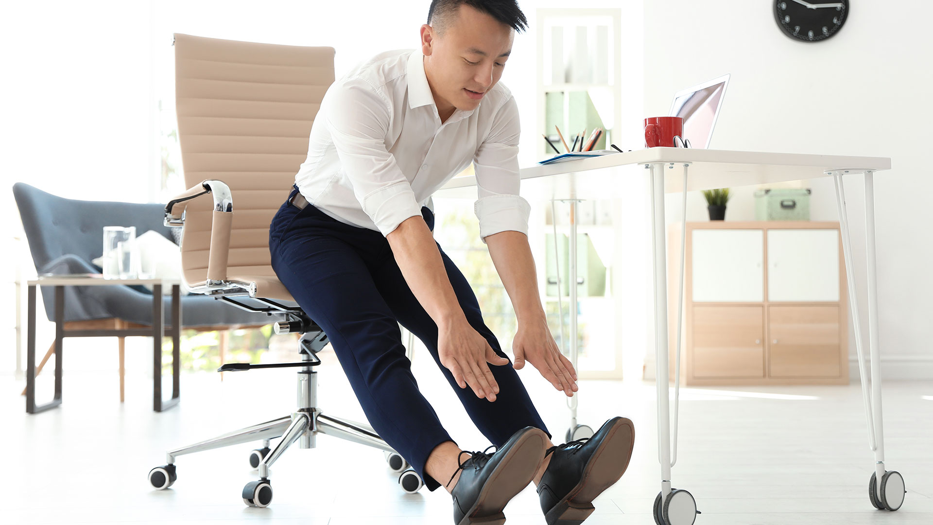 Man sits at the edge of his office chair and reaches his hands out to touch his toes with legs extended.