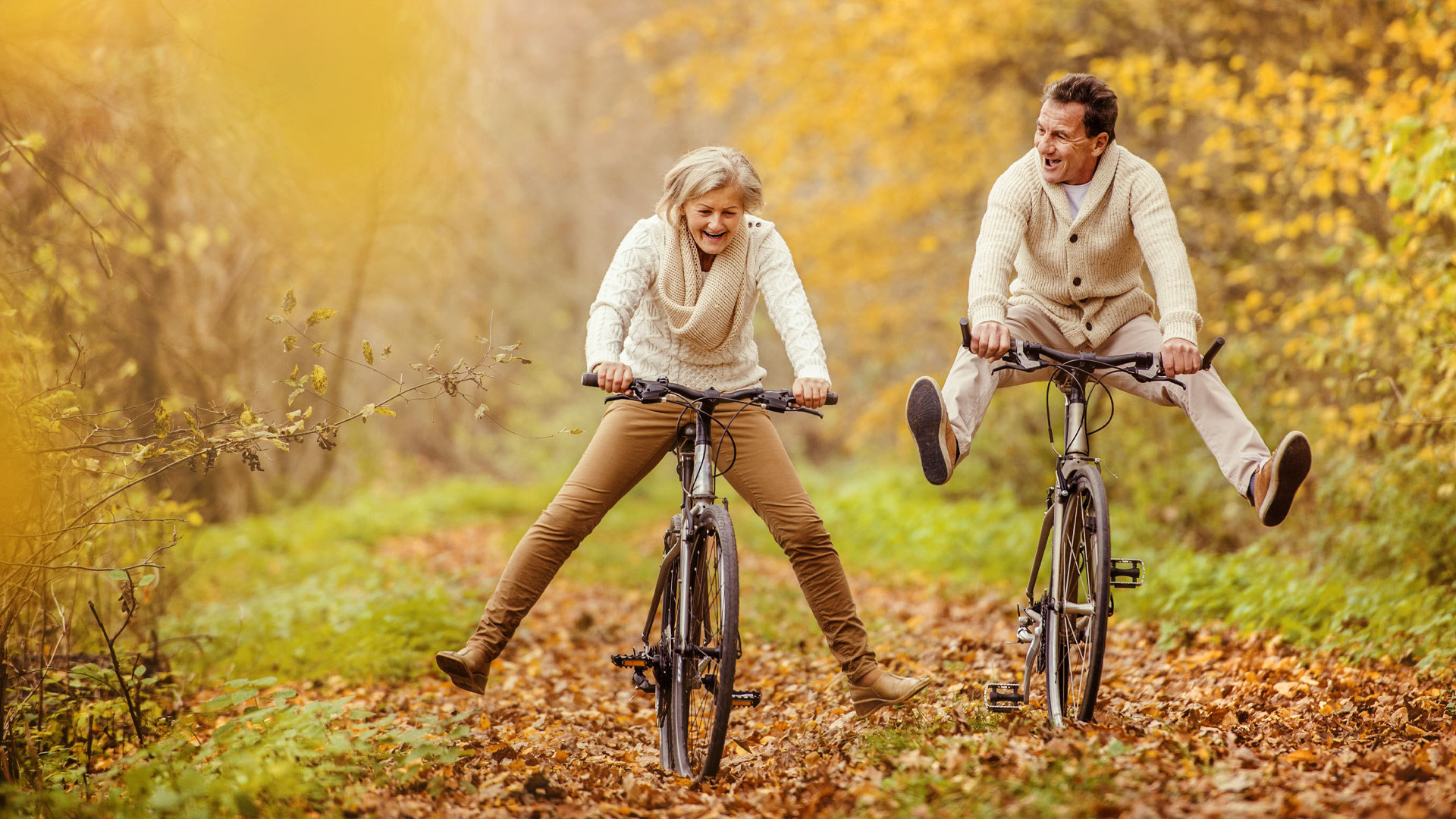 An older man and woman riding bikes through fall foliage with their feet raised playfully off the pedals.