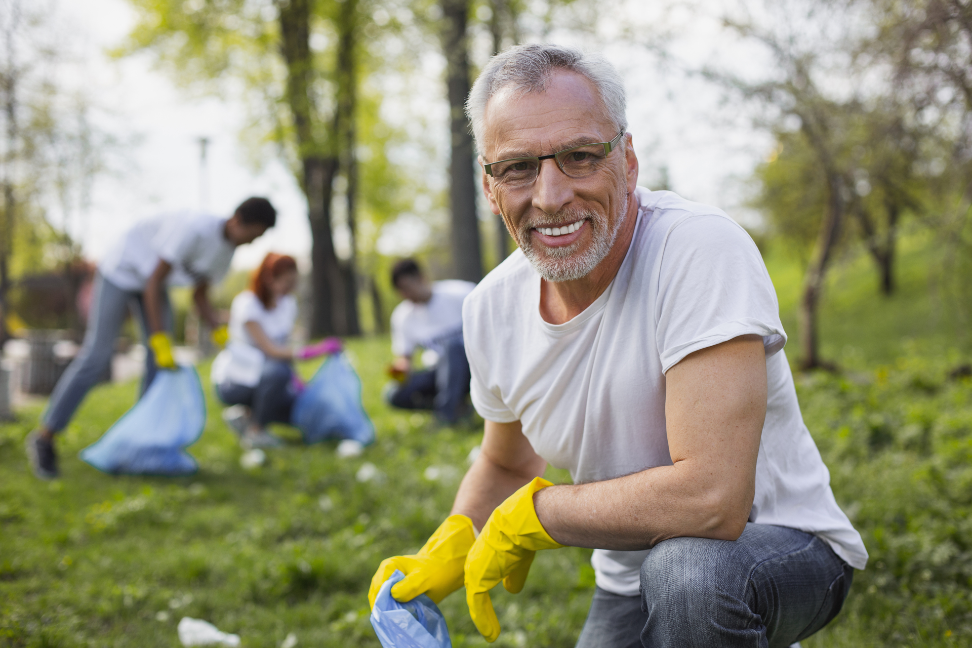 Middle aged man outside picking up trash volunteering