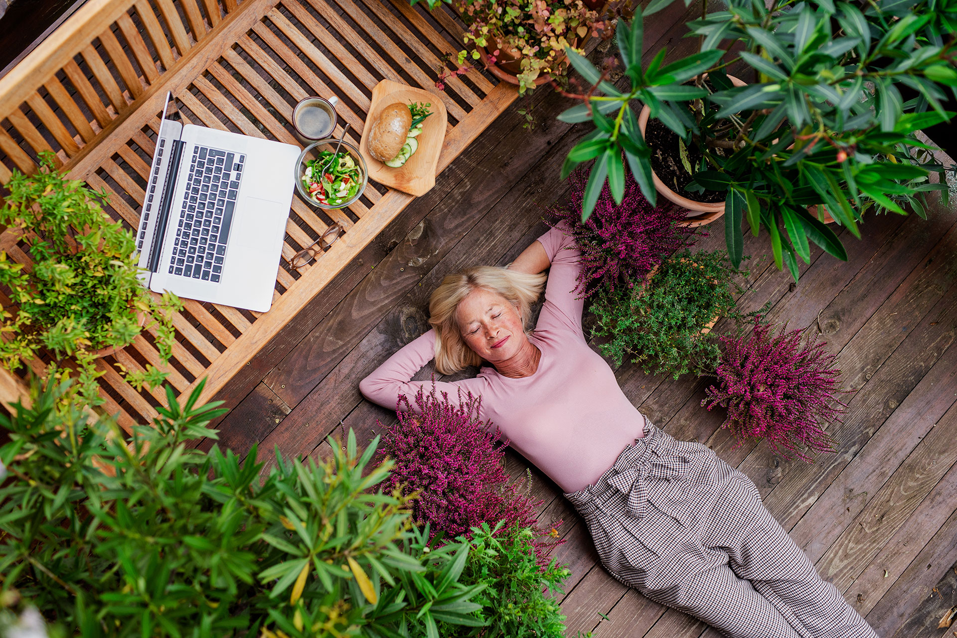 A woman has set her work laptop aside to take a break laying down on her wooden patio garden.