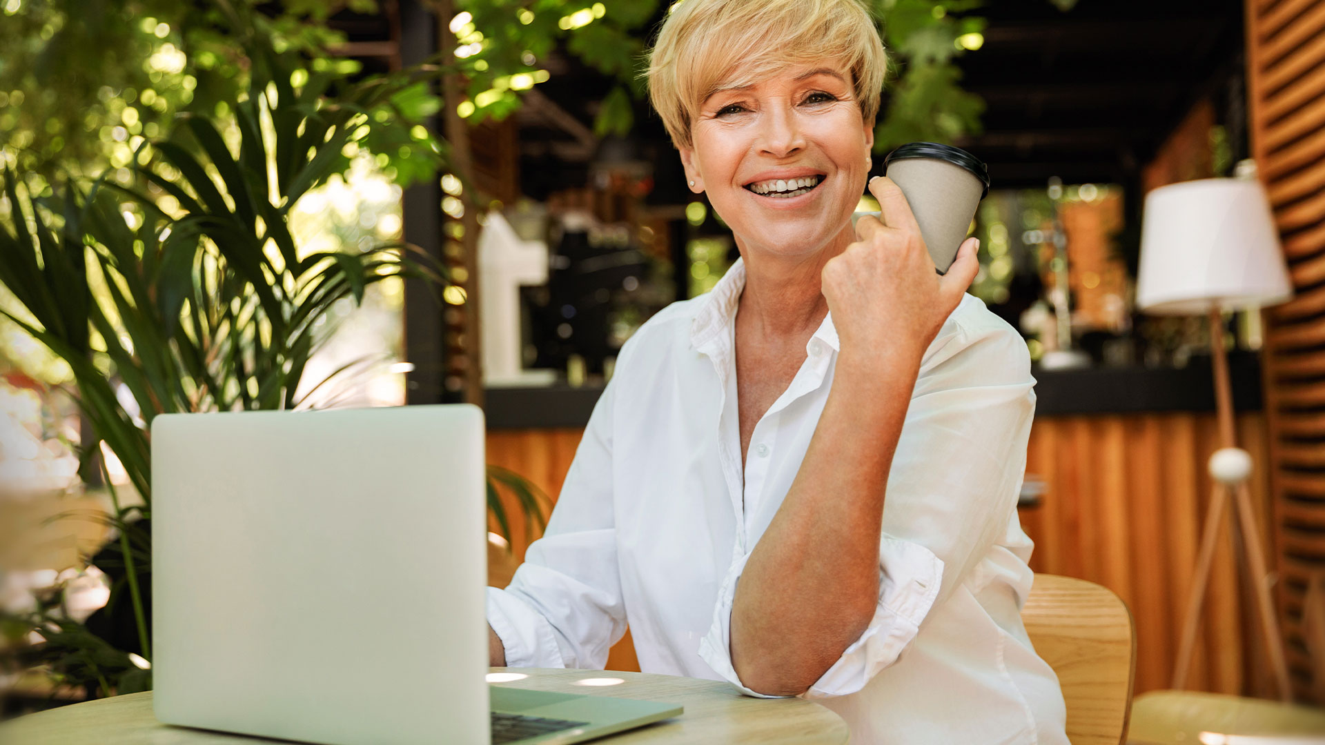 Professional woman sits outdoors working at her laptop with a coffee and smiles into the camera.