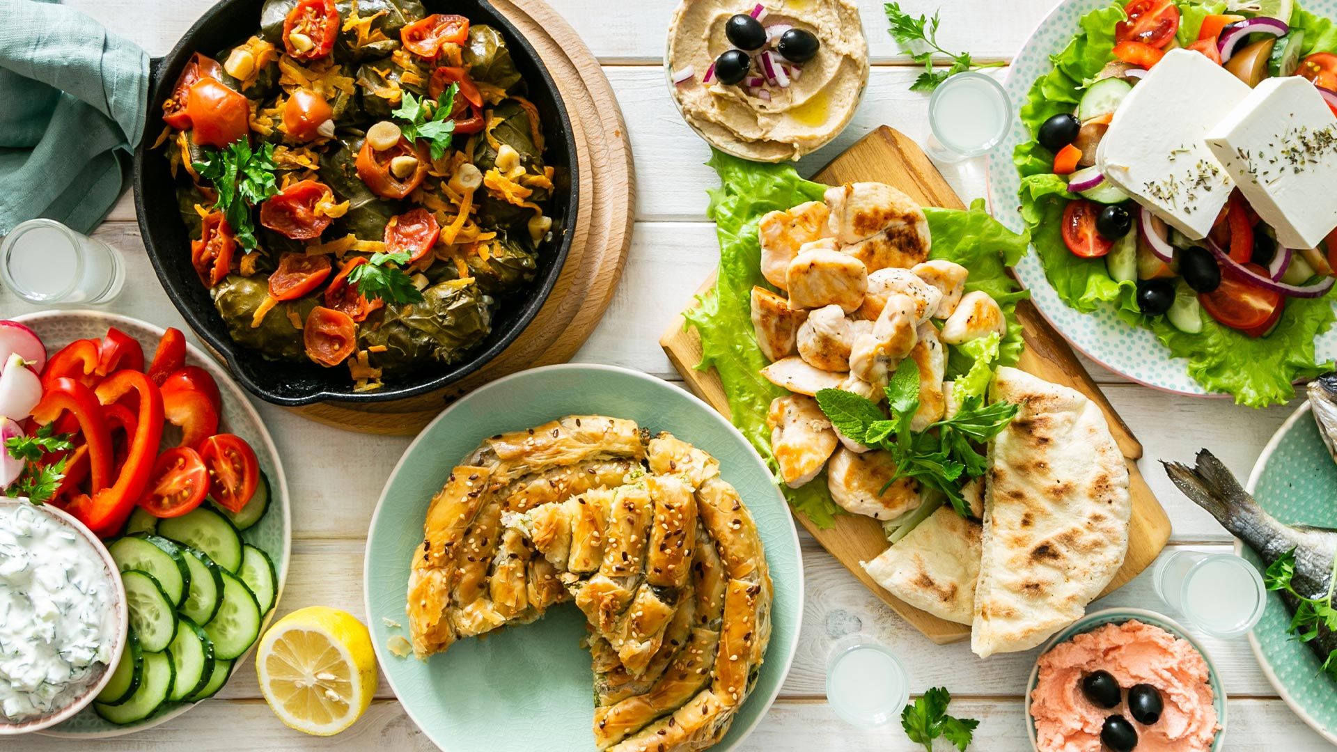 White Wood table with vibrant Greek Food, Salad, Pastry, Chicken and Yogurt Dip