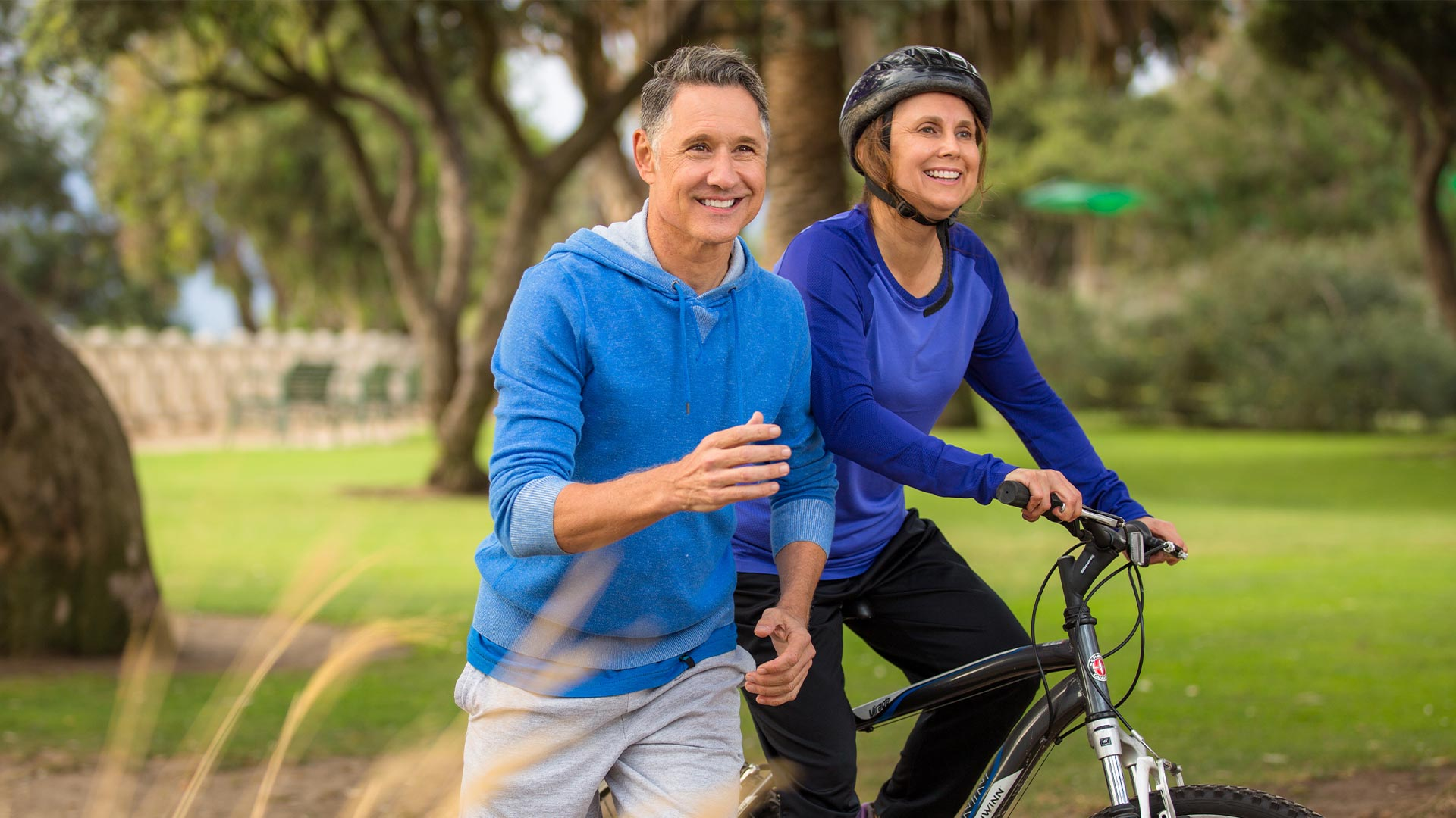 Couple in 50's in park, man with blue sweatshirt running & woman in blue shirt on her bike