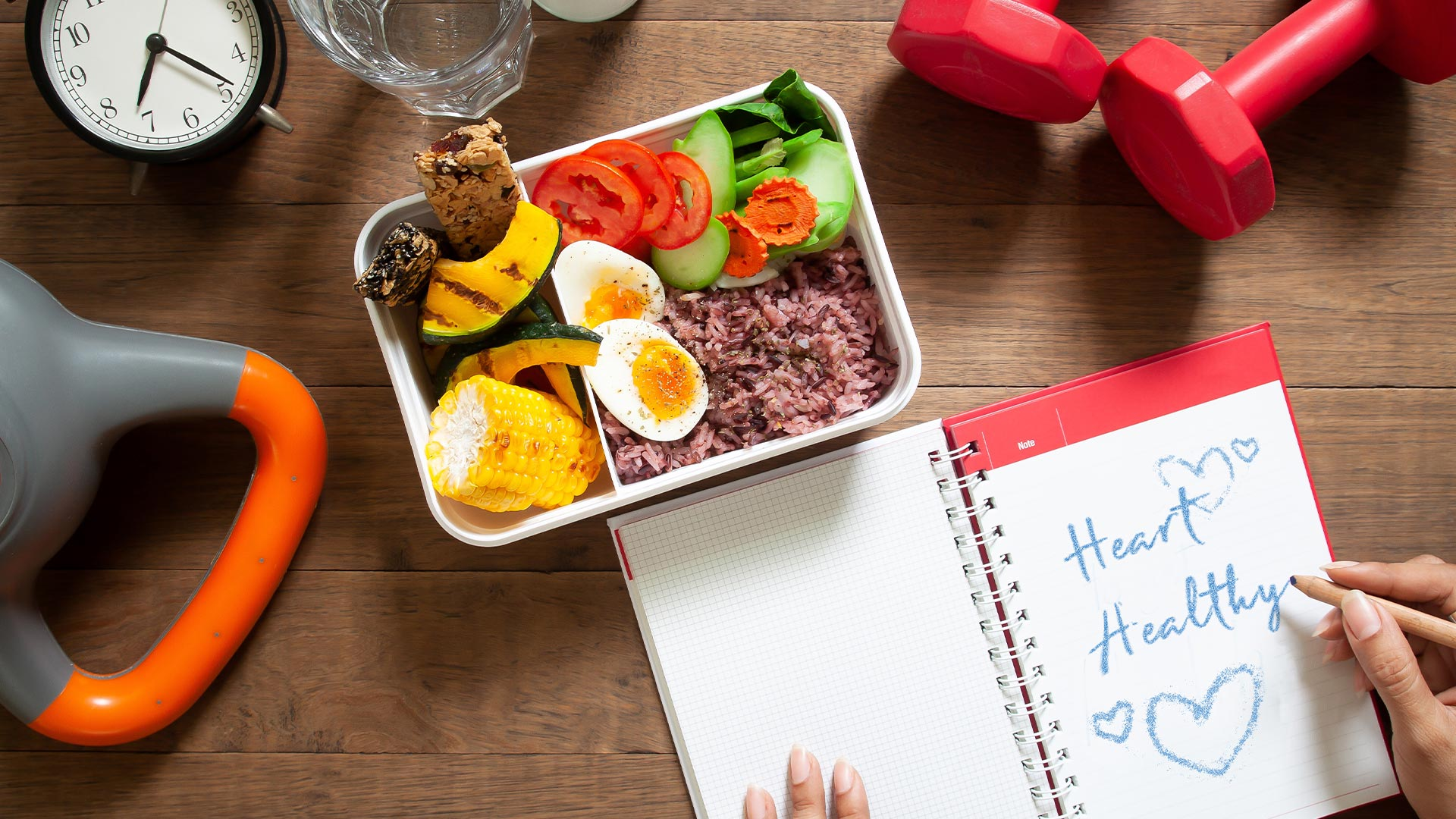 Wood table with power meal, weights, clock and notepad with words Heart Healthy written on it