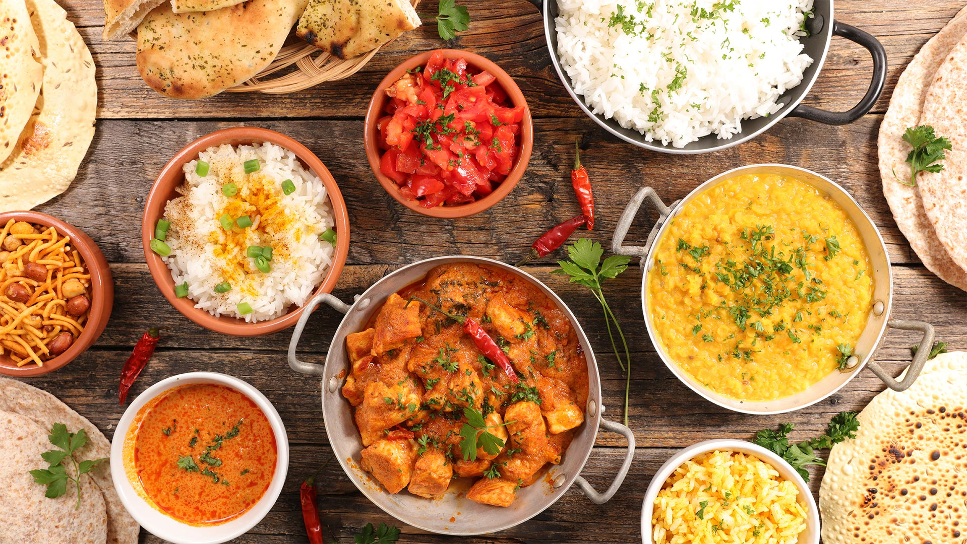 Bowls of indian food on wooden table, Tiki Masala, yellow rice, white rice, fresh chopped tomato and pita bread