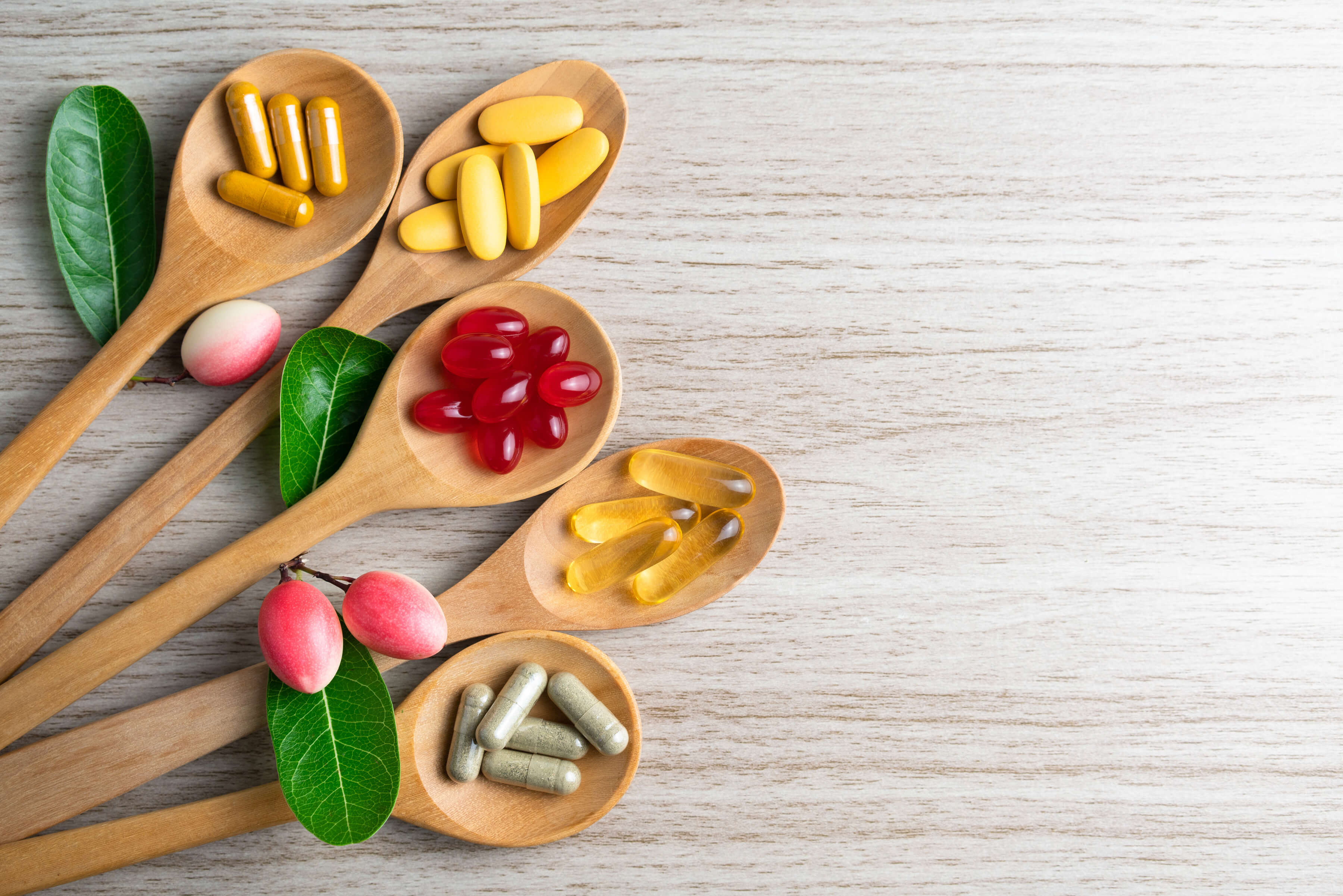 Supplement vitamins on wooden spoons on cooking board