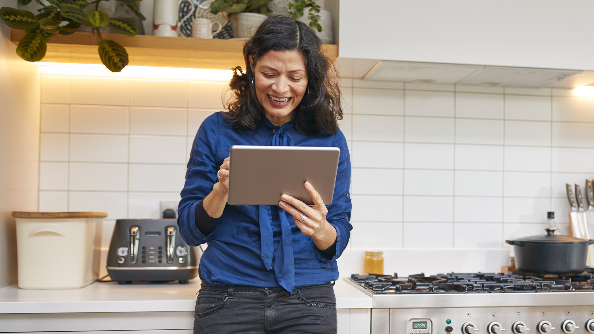 A woman with dark hair wearing a blue blouse stands leaned against her kitchen counter holding a tablet, smiling at the screen.