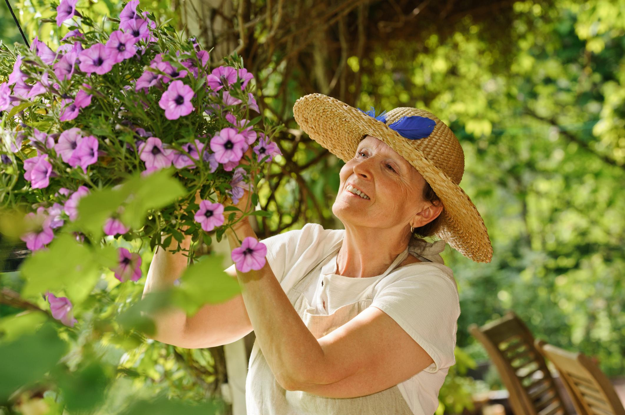 A woman trims flowers in her garden