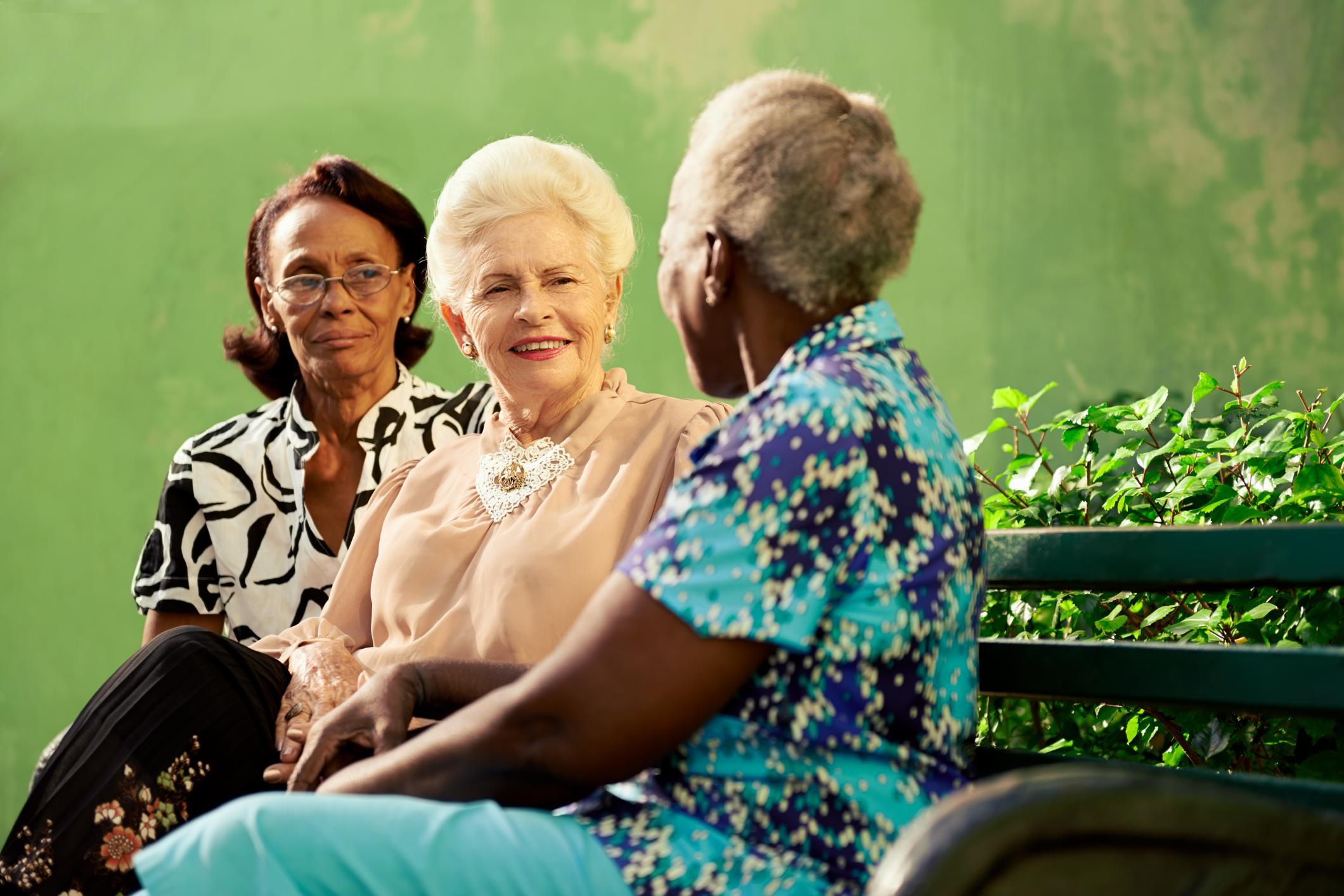 women talking on a bench